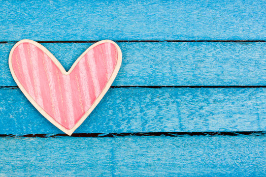 pink wooden heart on a blue background