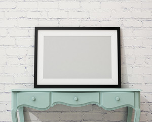 blank black picture frame on the white desk and wall