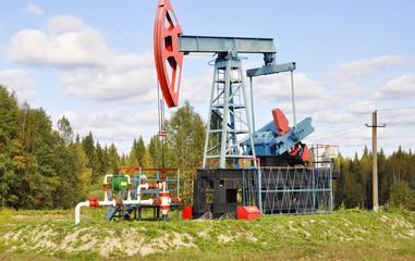 Станок качалка нефти на фоне зеленой травы и голубого неба
