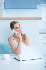 Smiling woman sitting at a desk taking call