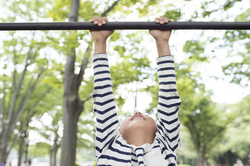 Boy hanging on horizontal bar