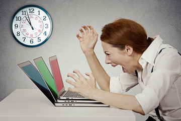 Angry businesswoman screaming at computer pressured by lack time