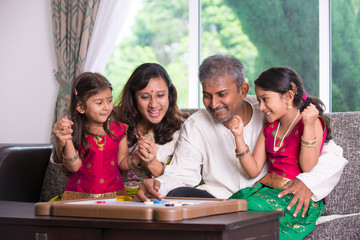 Indian family playing carrom game at home. Parents and children