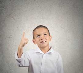 Boy pointing with index finger up, looking up at copy space