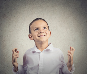 Child crossing fingers isolated on grey wall background