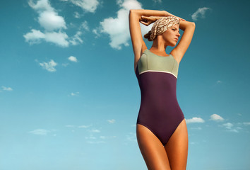 beautiful woman with tan in swimsuit against the sky.