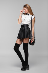 Beautiful woman is in fashion style in black mini skirt.
