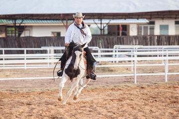 A cowboy riding a horse in his farm