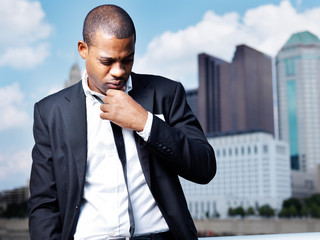 african man in suit thinking in front of city