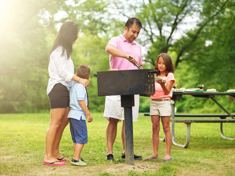 family barbecue - dad giving daughter cooked food