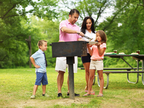 family barbecue - dad giving kids food