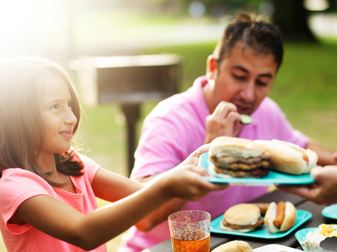 father and daughter eating together at barbecue cookout