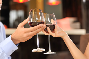 Two people toasting with wine glasses.