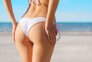 Sexy woman's buttocks in white bikini on the beach