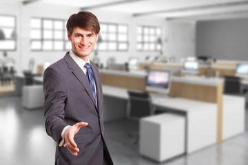 Geschäftsmann vor Bürohintergrund mit Handschlaggeste