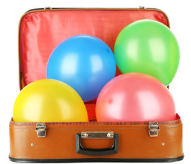 Pile of balloons of different colors in old suitcase,