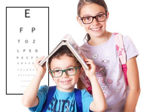 Bambini con occhiali e tabella per il controllo della vista