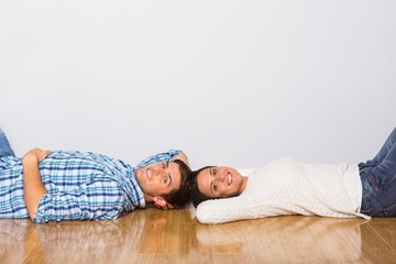 Young couple lying on floor smiling