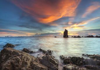 sunset waves lash line impact rock on the beach
