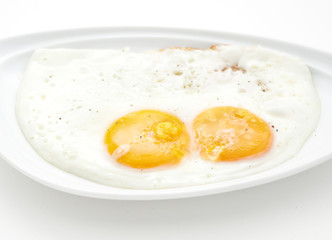 Two scrambled eggs on a white plate