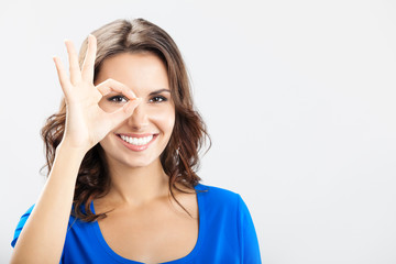 Young woman showing okay gesture, over grey