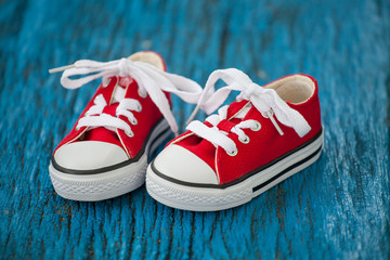 Red baby sneakers on wooden blue background