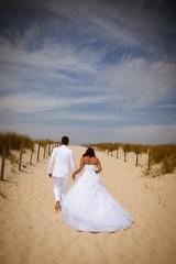 Mariés habillés en blanc sur la plage