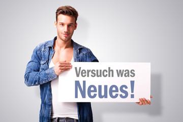 """junger Mann hält Schild mit Text """"Versuch was Neues!"""""""