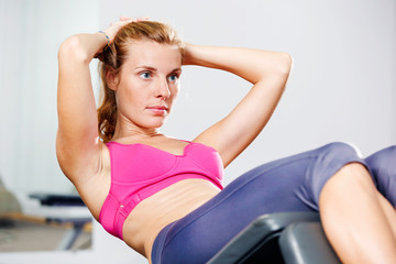 Beautiful young athletic woman doing sit-ups in a bench.