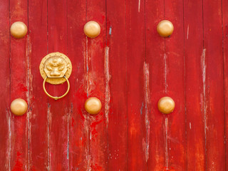 ancient red wooden gate with lion door knocker