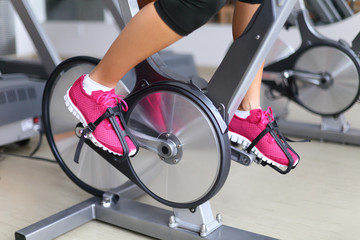 Exercise bike with spinning wheels - woman biking