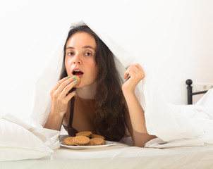 Girl eating cookies in bed