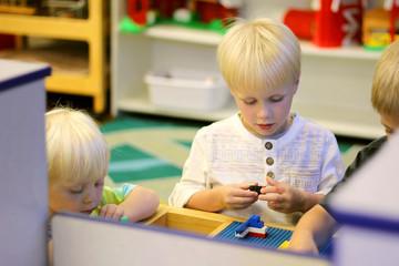 Young Preschool Children Playing Building Blocks in School Class