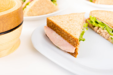 ham and lettuce sandwich on a white plate