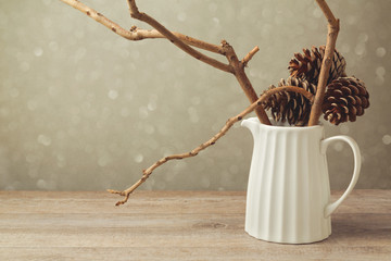Christmas table decoration with jug and winter branches