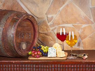 Wine, cheese, grapes and old wooden barrel; still life