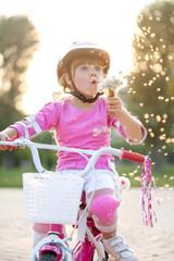 blond little girl on her bike blowing a dandelion