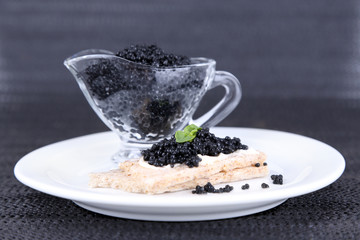 Slice of bread with butter and sauceboat with caviar