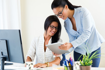 Two business woman working in office with digital tablet.
