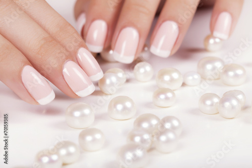 Wall mural Beautiful woman's nails with french manicure and pearls.