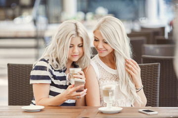 Two girls drink coffee and use the phone