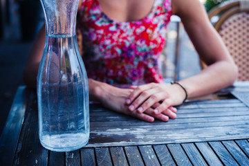 Woman sitting at table with jug of water