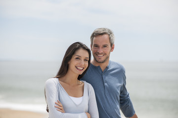 beautiful couple on the beach smiling and looking at camera