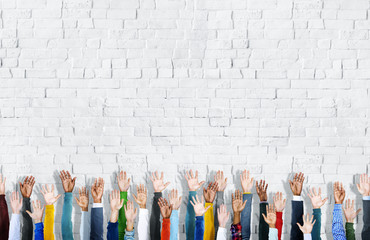 Diverse Hands Raised on a Brick Wall Background