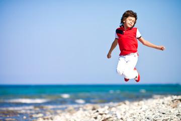 Мальчик на берегу синего моря в прыжке