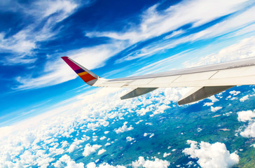 Wing of the plane on sky background - plane wing with cloud patt