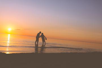 Senior couple kissing at sunset