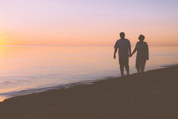 Senior couple walking along the beach