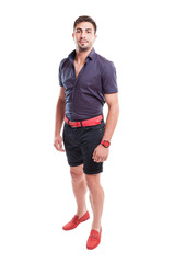 Man wearing shorts, purple shirt and pink belt and shoes.