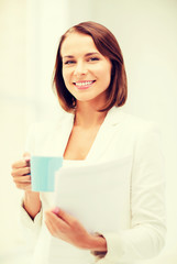 woman with cup of coffee and folders